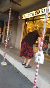 L' anziana cliente, con le buste della spesa, è in difficoltà a salire lo scalino che porta al negozio di elettricista