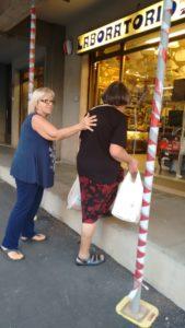 Alba Tiezzi, titolare del negozio di elettricista in via Andreotti è costretta ad aiutare a salire una cliente, in seguito al grande scalino sul marciapiede lasciato dopo i lavori di installazione della fibra ottica
