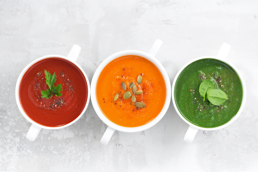 assortment of colorful vegetable cream soup on a white background, horizontal