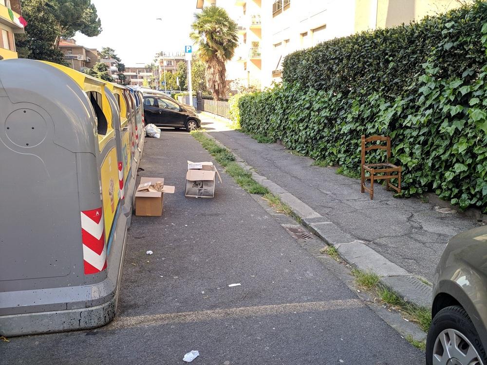 Via dell'Olivuzzo, una sedia rotta e vari scatoloni ostruiscono il passaggio sul marciapiede alle carrozzine
